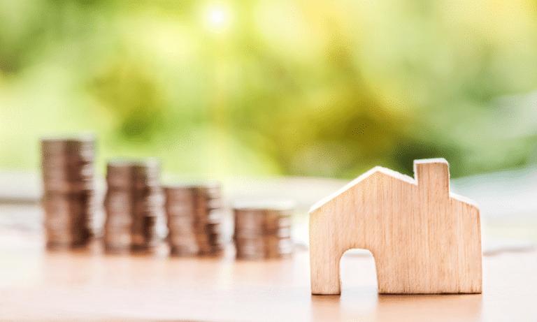 Ein miniatur Holzhaus neben Hausgeld