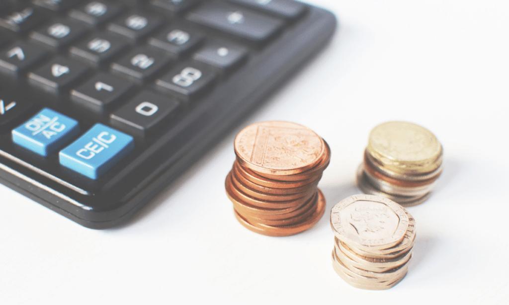 Geldmünzen neben einem Taschenrechner